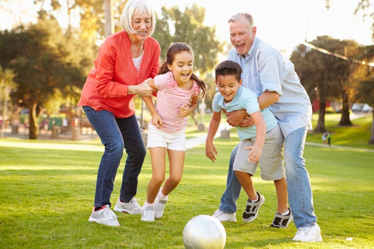 Grandparents and grandkids playing on the grass