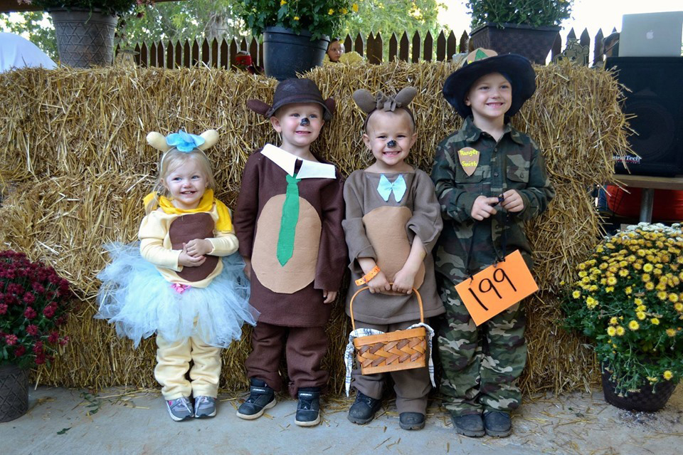 Children in Halloween costumes by bales of hay
