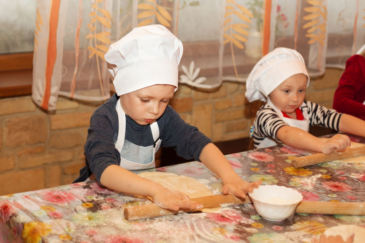 Two small boys wearing chef's hats rolling Italian pasta