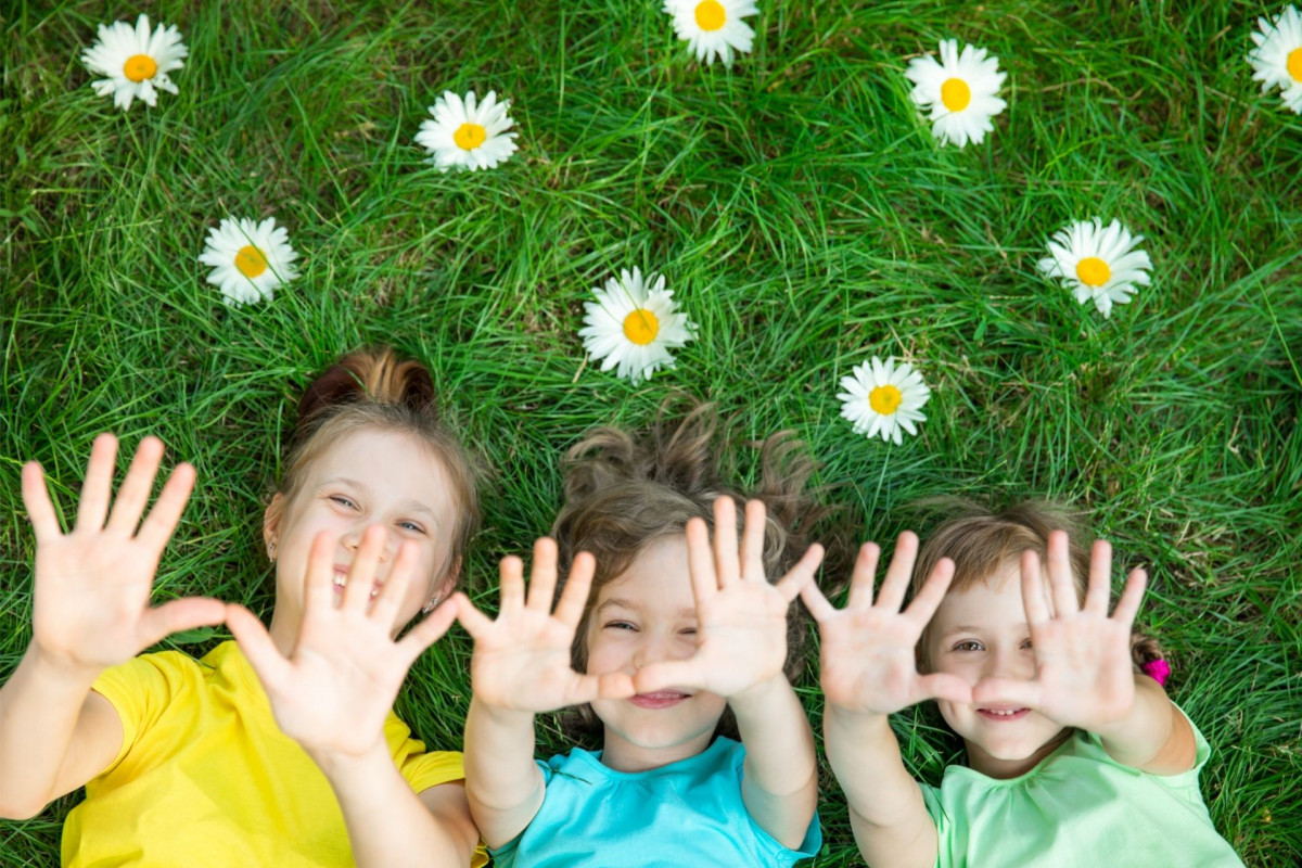 Kids on the grass with daisies
