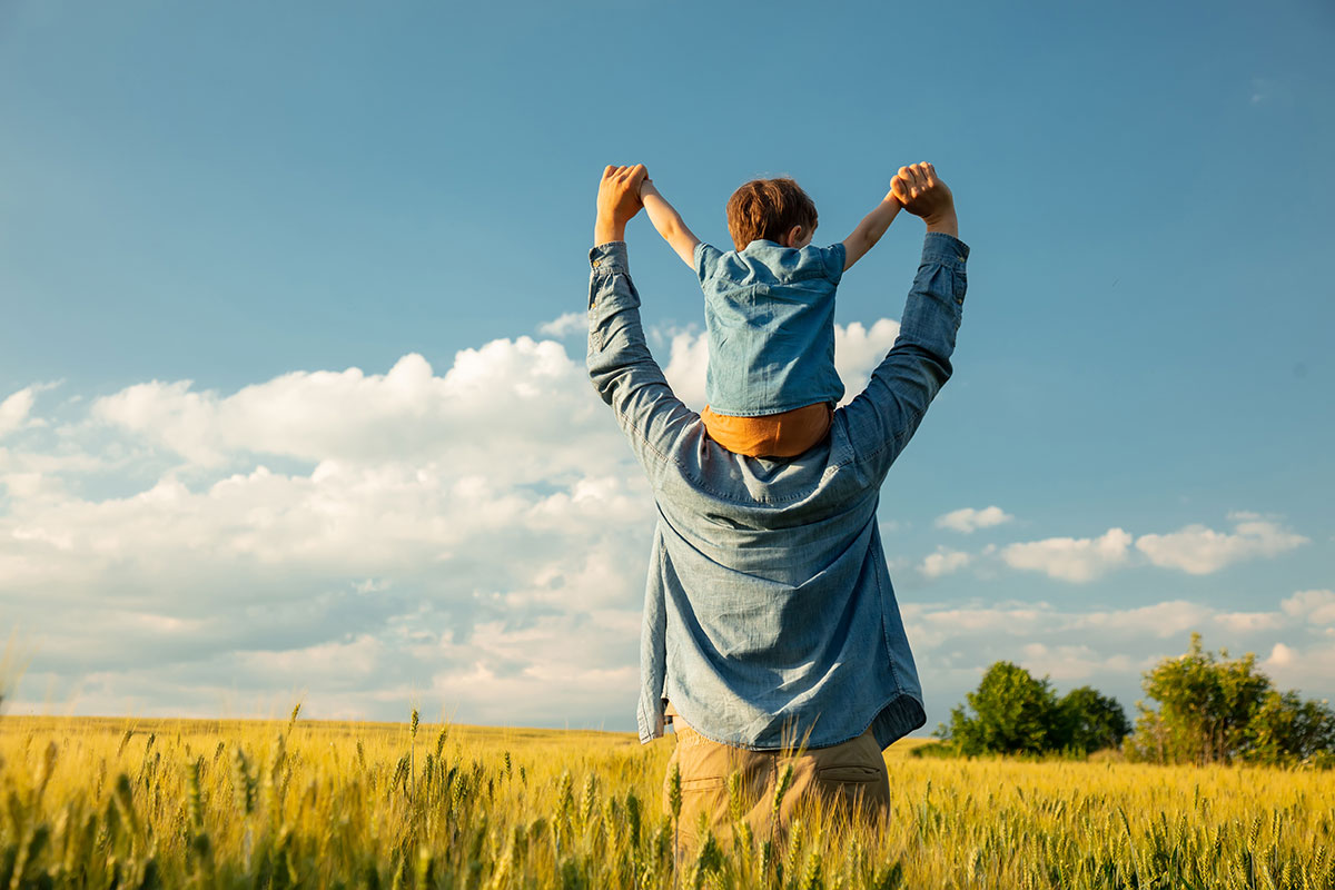 Dad with son on his shoulders in a field