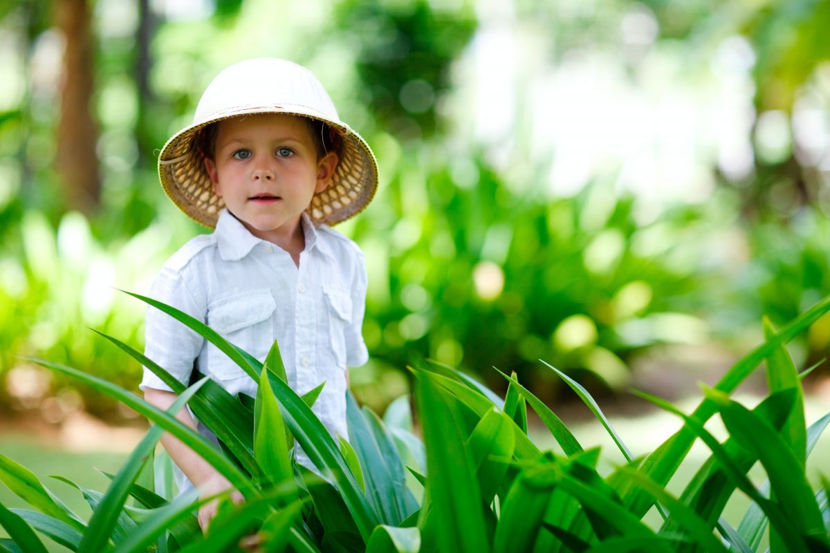 Boy wearing safari hat in tall grass