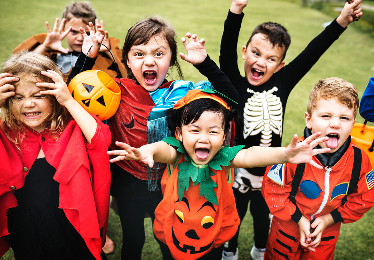 A group of excited kids in Halloween costumes